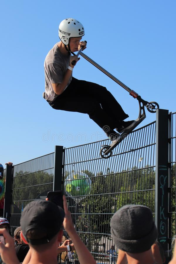 A competitor performing in Pro-series of Finnish Scooter Championships. FinScooter Summer Jam sport event was held in Leppaevaara skate park in Espoo, Finland stock photos