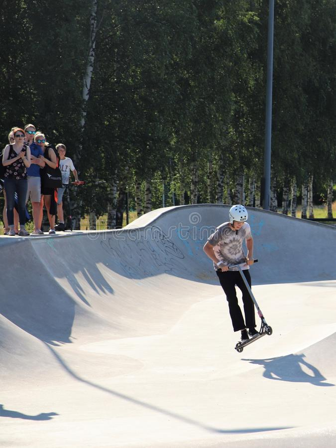 A competitor performing in Pro-series of Finnish Scooter Championships. FinScooter Summer Jam sport event was held in Leppaevaara skate park in Espoo, Finland royalty free stock photos