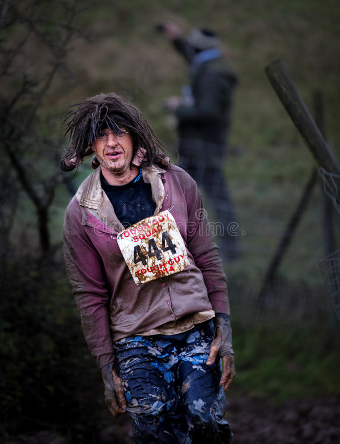 Competitor 444 at 2014 Tough guy obstacle race. In fancy dress royalty free stock image