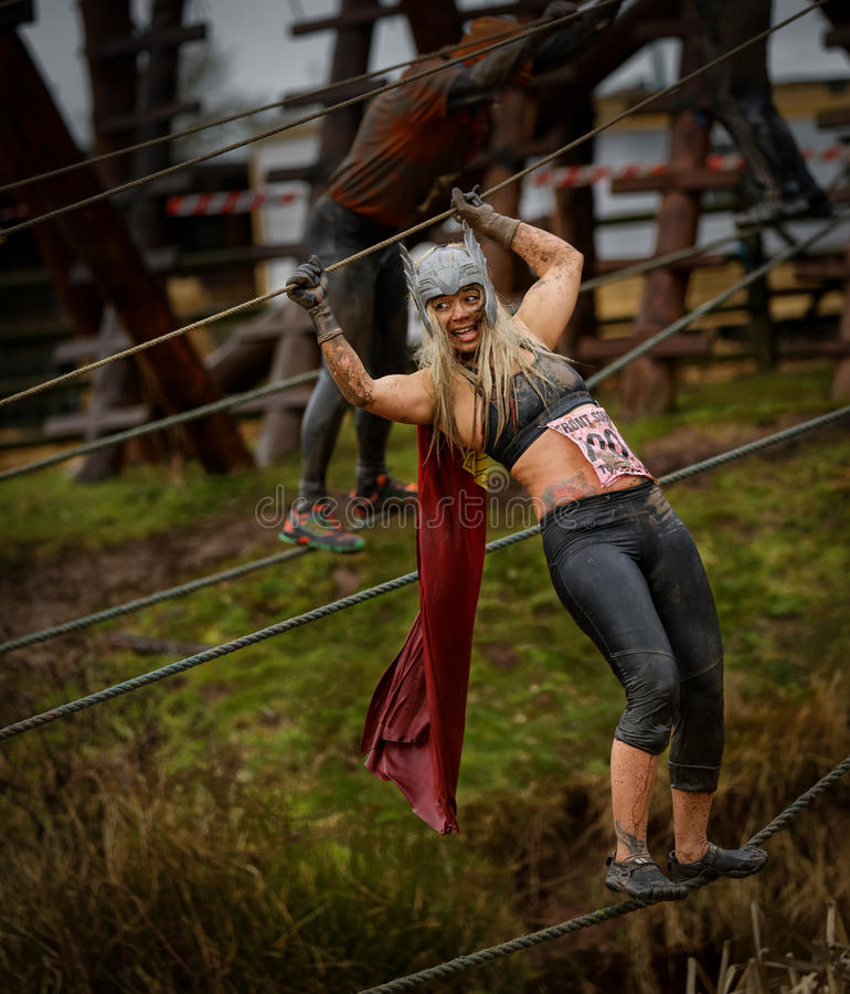 Competitor at 2014 Tough guy obstacle race. In fancy dress and balancing on ropes stock photography