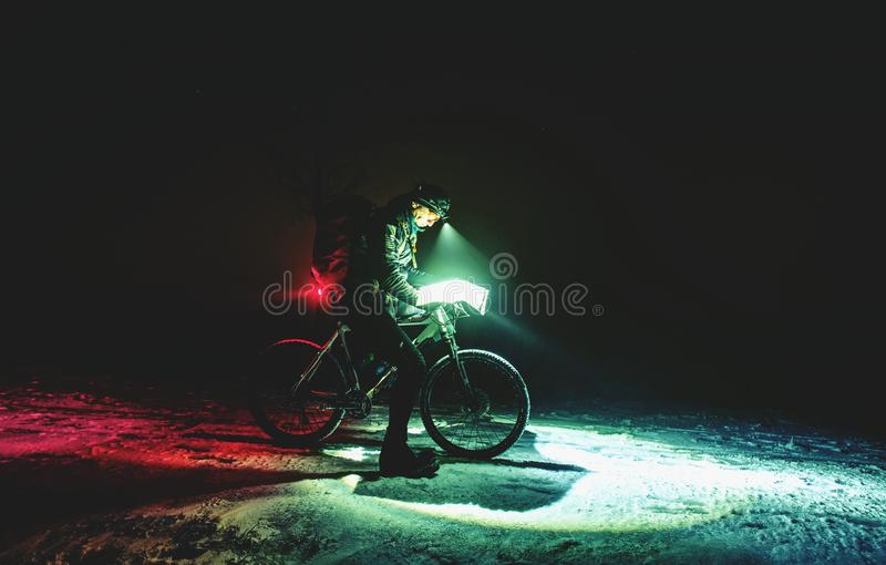 Competitor of winter night mtb race stop for possition control. Biker with white fat bike looking into map in night while snowing stock photo