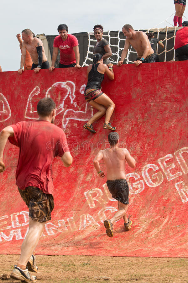 Competitors Attempt To Climb Wall In Extreme Obstacle Course Race stock images