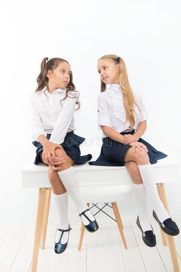 Competitors. Every day better. Little schoolgirls classmates friendly kids. Schoolgirls friends sit on desk. Best stock photos