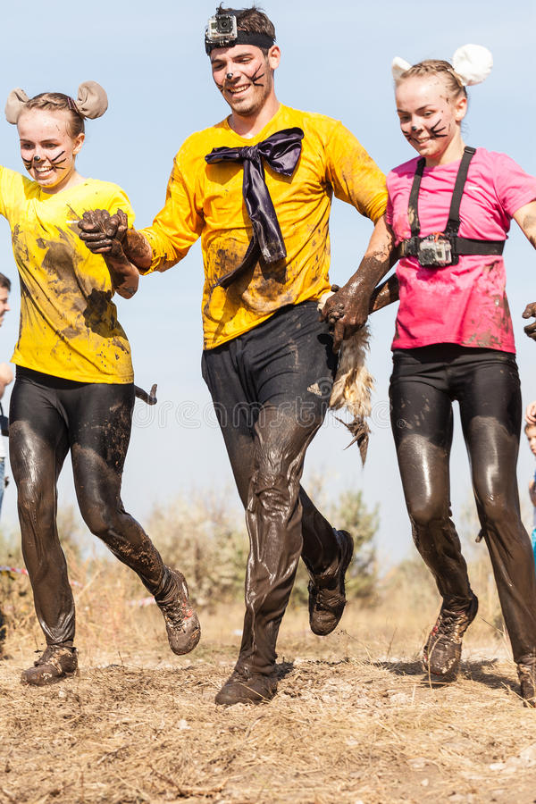 Competitors in Hryaschevka Challenge Extreme Marathon, Tolyatti, Russia. Man and women wearing costumes covered in mud during the running of the International stock images