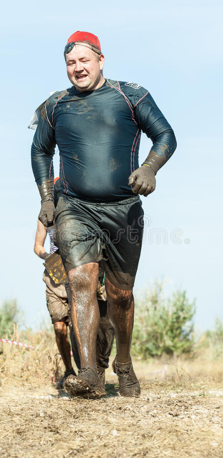 Competitors in International Extreme Marathon, Tolyatti, Russia. Man covered in mud during the running of the International Extreme Marathon Hryaschevka stock image