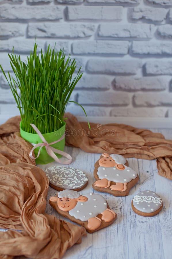 compisition пасха Славные застекленные печенья имбиря в форме овец кладя на деревянный стол около зеленой травы стоковые фото