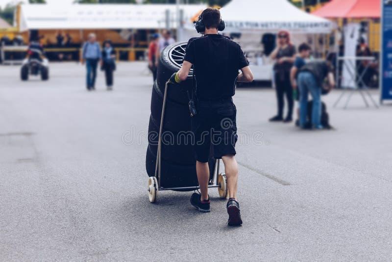 Compitiendo con las ruedas y los neumáticos transportados por el equipo de la raza durante una competencia imagen de archivo libre de regalías