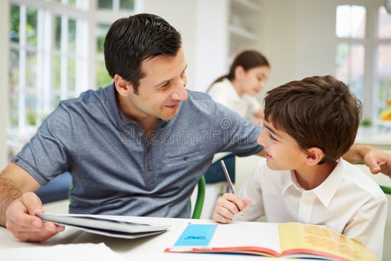 Compito di Helping Son With del padre facendo uso di una compressa fotografia stock