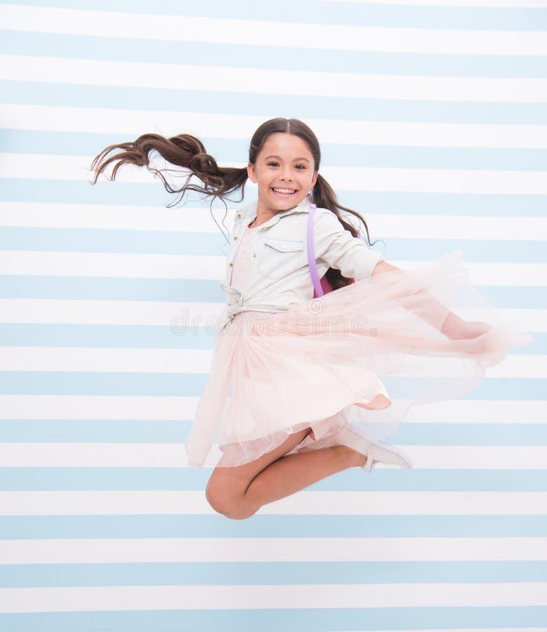 Complètement de l'énergie La coiffure heureuse de queue de cheval de visage de fille saute en air Badinez la robe élégante de fil photographie stock