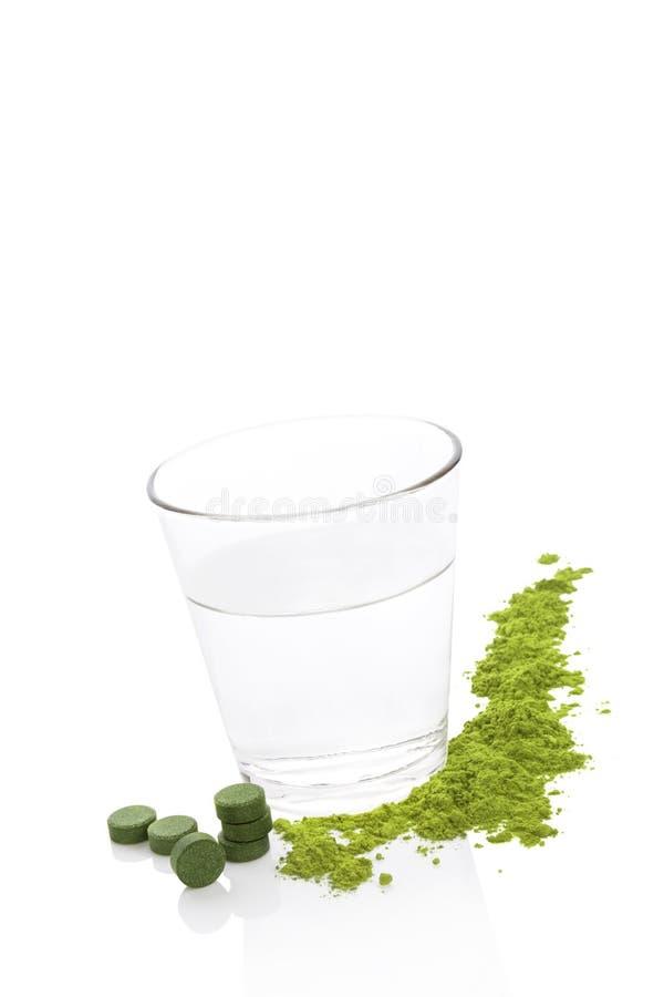 Compléments alimentaires verts et un verre de l'eau photos stock
