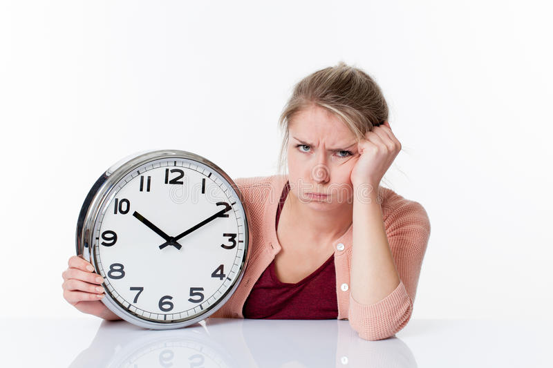 Complaining beautiful young woman holding a clock royalty free stock photo