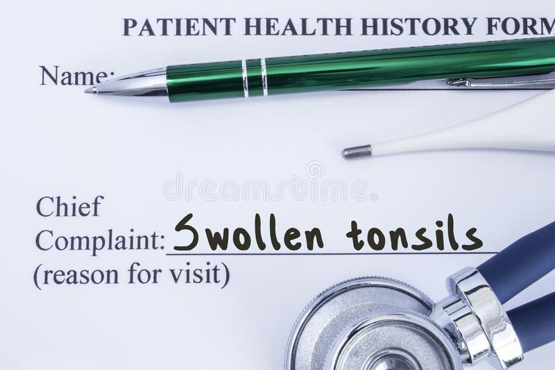 Complaint of Swollen Tonsils. Paper health history form, which is written on patient`s chief complaint of Swollen Tonsils, surroun. Ded by stethoscope stock images