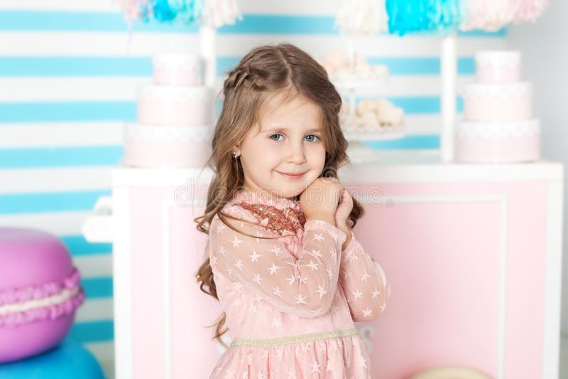 Compleanno e concetto di felicità - bambina felice con i dolci sui precedenti della barra di caramella Ritratto di bella bambina immagine stock