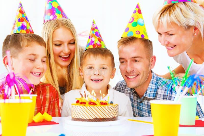 Compleanno Il ragazzino spegne le candele sulla torta di compleanno immagine stock libera da diritti