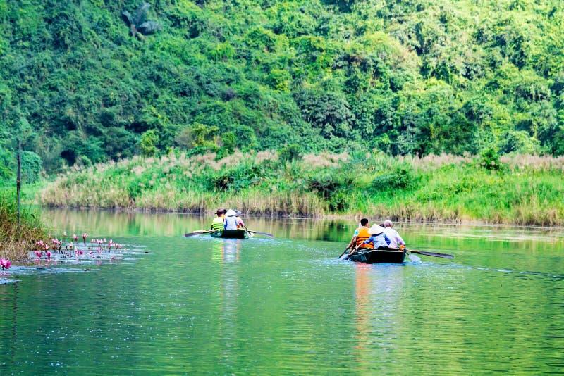 COMPLEJO de TRANGAN ECO-TOURIST, VIETNAM - 27 de noviembre de 2014 - turistas que viajan en barco en la corriente del complejo fotos de archivo libres de regalías