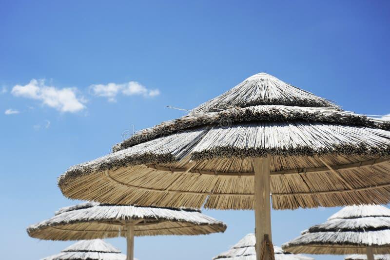 Complejo playero hermoso con los paraguas blancos de la paja en un cielo azul y las nubes blancas Vida de la playa y concepto de  imagenes de archivo