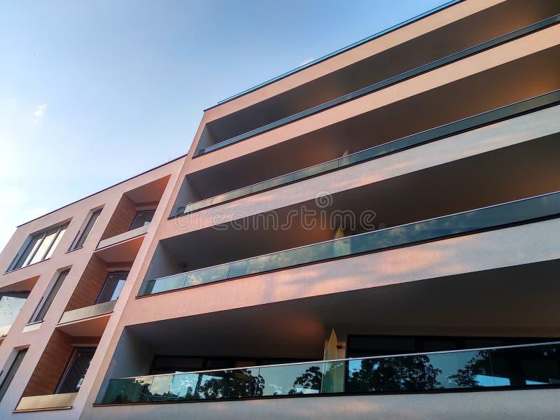 Complejo residencial de varios pisos moderno en la ciudad Windows y logias de una casa en la puesta del sol entre los árboles ten imagen de archivo libre de regalías