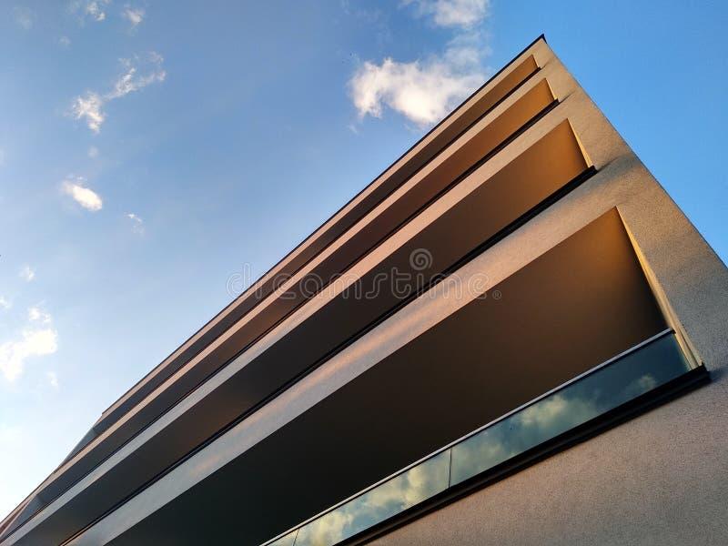Complejo residencial de varios pisos moderno en la ciudad Windows y logias de una casa en la puesta del sol entre los árboles ten imagen de archivo