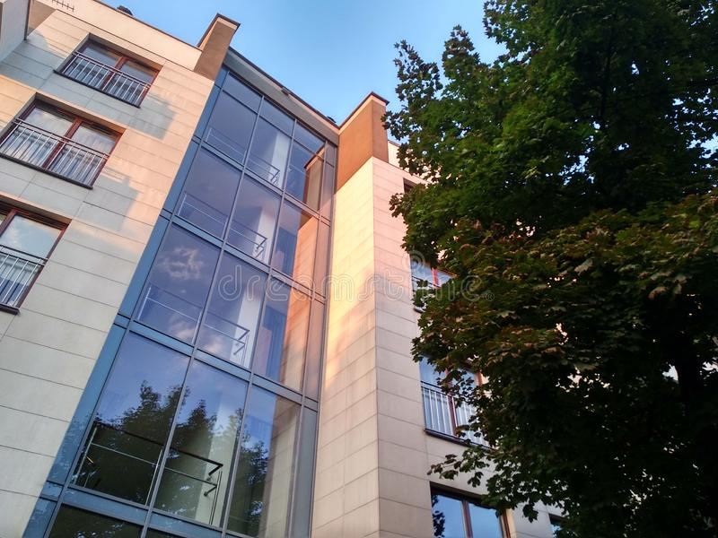 Complejo residencial de varios pisos moderno en la ciudad Windows y logias de una casa en la puesta del sol entre los árboles ten fotografía de archivo libre de regalías