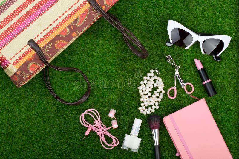 complementos - el bolso, el cuaderno de notas, las gafas de sol, los auriculares, el lápiz labial y el otro esencial en la hierba foto de archivo libre de regalías
