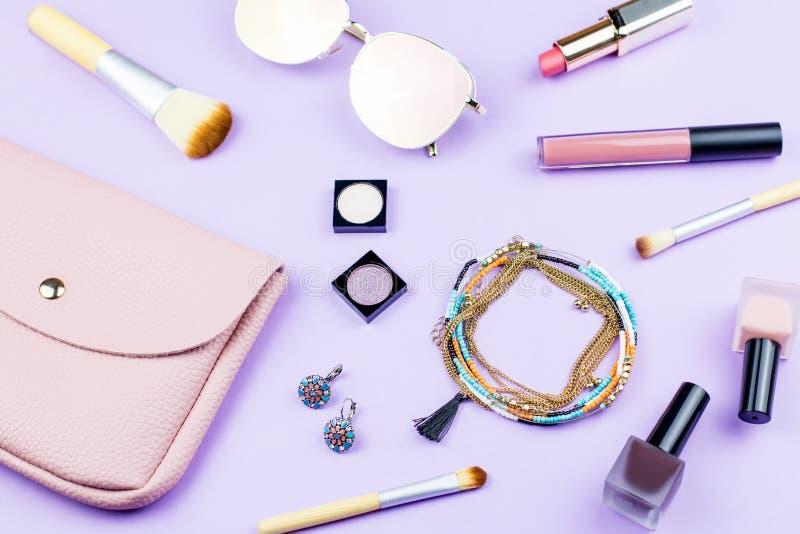 Complementos femeninos en fondo en colores pastel El monedero rosado, gafas de sol duplicadas, joyería, compone artículos foto de archivo
