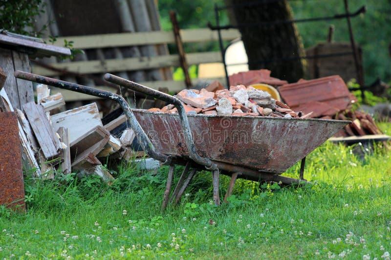 Completamente caricato con il materiale da costruzione ha arrugginito il carretto della costruzione della carriola con il pneumat fotografia stock
