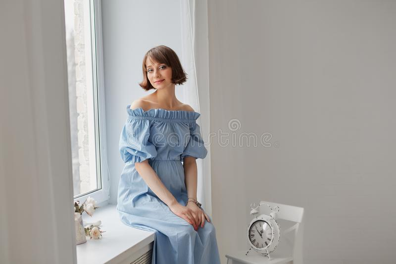 Complete family. Pregnancy, motherhood, people and expectation concept - close up of happy pregnant woman with big belly at window. Last months of pregnant royalty free stock image