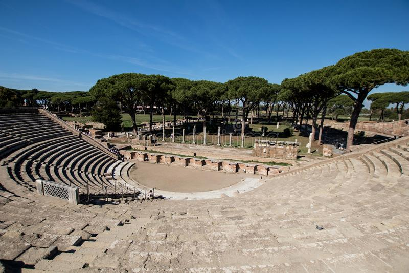 Almost complete Roman theater in Ostia antica. Drama place in an. Cient Rome with sea pines in background and ruins stock image
