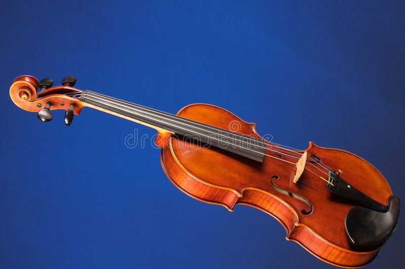 Complete Violin Viola On Blue. A complete violin viola isolated against a blue background in the horizontal format with copy space royalty free stock photos