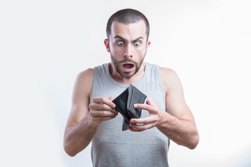 Completely broke man. Broke man gasping in shock when he sees he has no money in his wallet stock image