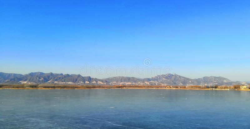Completely frozen Beijing Qinglong Lake. Qinglong Lake, located in the southwest of Beijing, has been completely frozen, and a few people are fishing in the ice royalty free stock photos