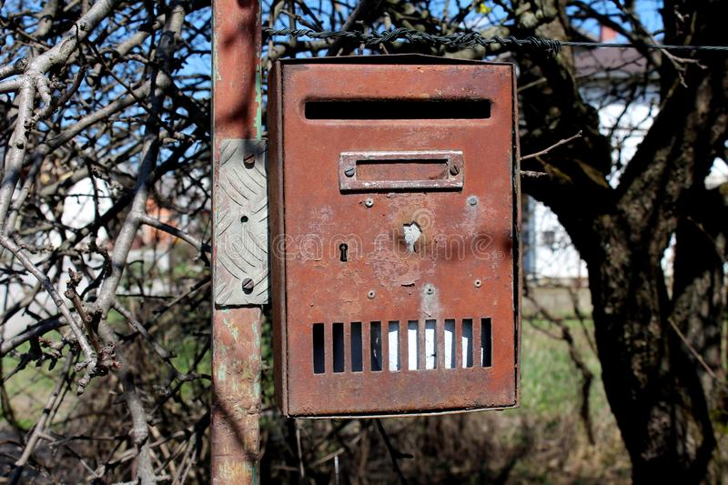 Completely rusted mailbox with letter inside mounted on improvised metal pipe in front of dense branches and trees without leaves stock image