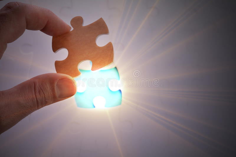 Completing the last piece of jigsaw puzzle royalty free stock photography