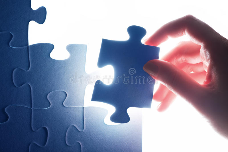 Completing the last piece of jigsaw puzzle. Solution stock images