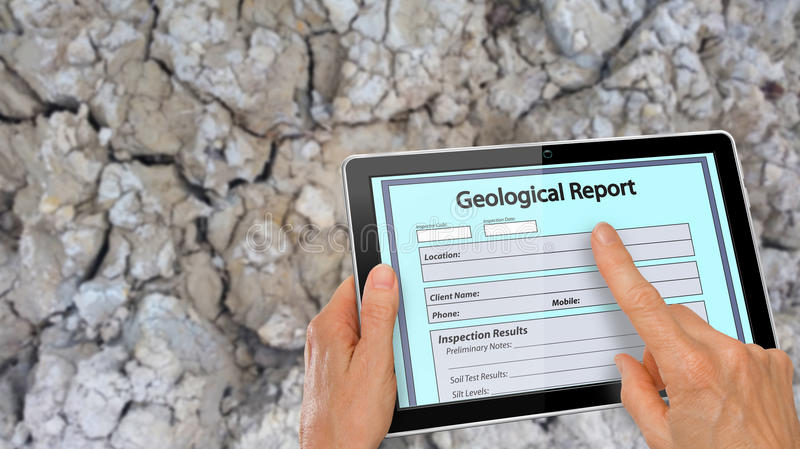 Completing online Geological Report on a computer tablet. Hand completing online Geological Report on a computer tablet - infront of clay soil background stock photo
