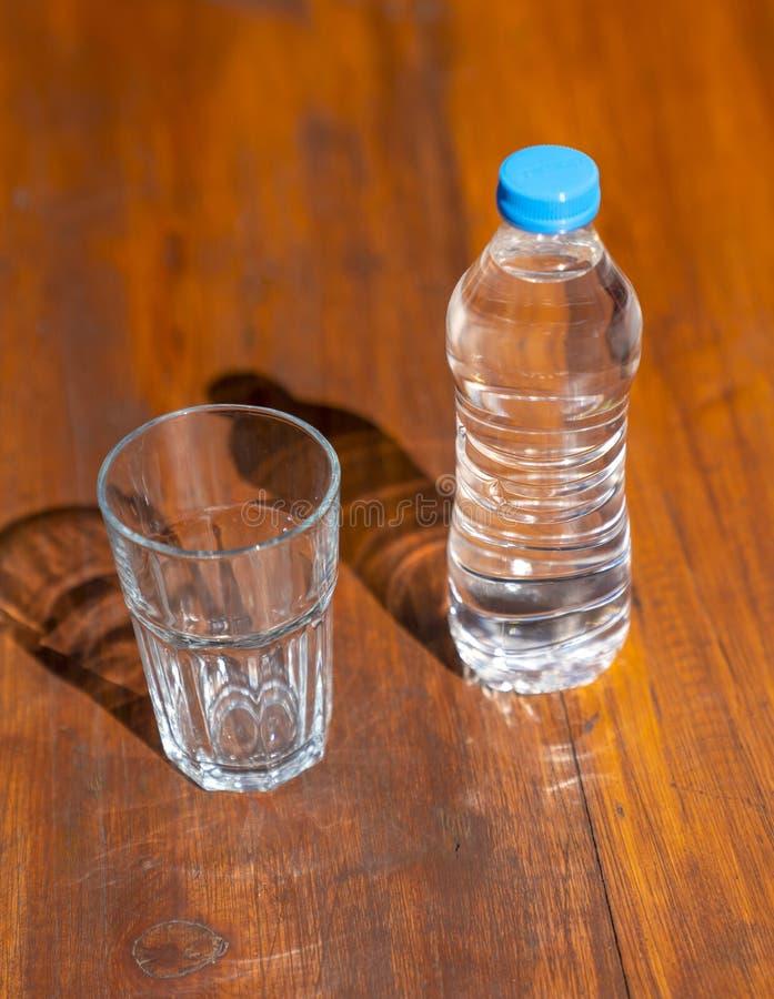 Completo da água potável fresca na garrafa plástica e em um vidro da água na tabela de madeira marrom foto de stock