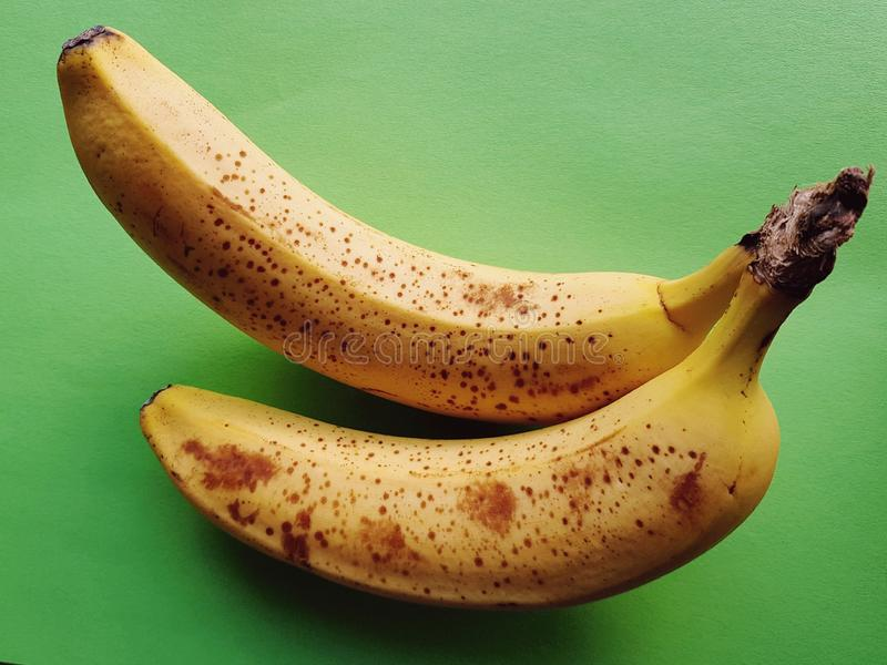 Completo das vitaminas! Close up de bananas maduras deliciosas sobre o fundo verde fotografia de stock royalty free