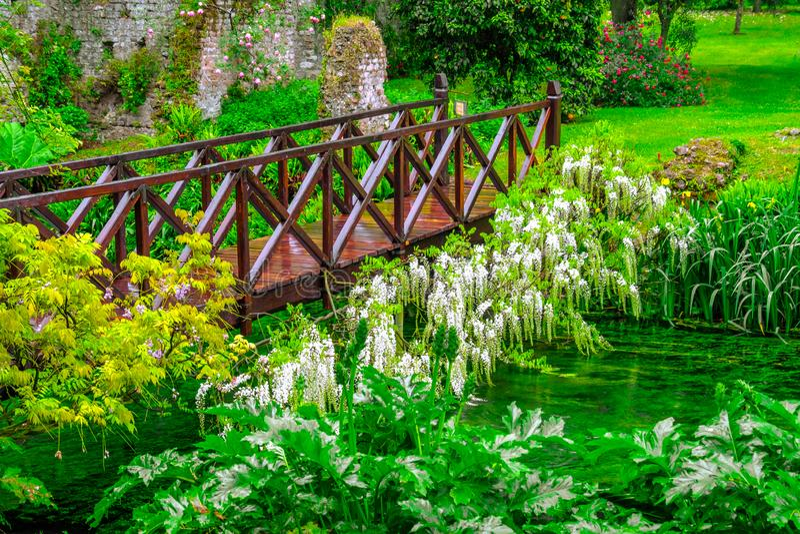 Completo de madeira vívido de Green River da ponte do conto de fadas das flores no jardim decorativo foto de stock royalty free