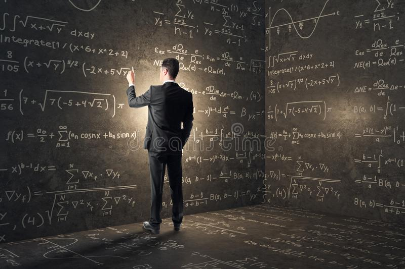 Complex algorithm and math concept. Back view of young businessman in concrete corner with mathematical formulas. Complex algorithm and math concept stock photography