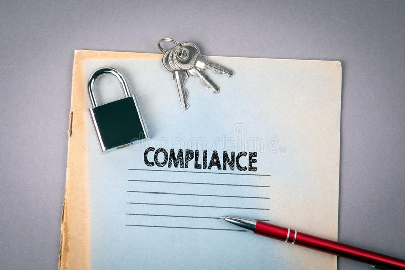 Compliance. Padlock, notebook and pen on gray desk. Business concept stock photography
