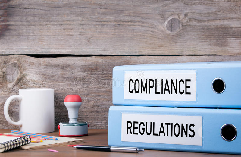 Compliance and Regulations. Two binders on desk in the office. stock image