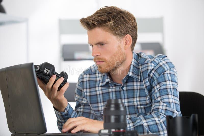 Componente d'esame della macchina fotografica del tecnico maschio fotografia stock