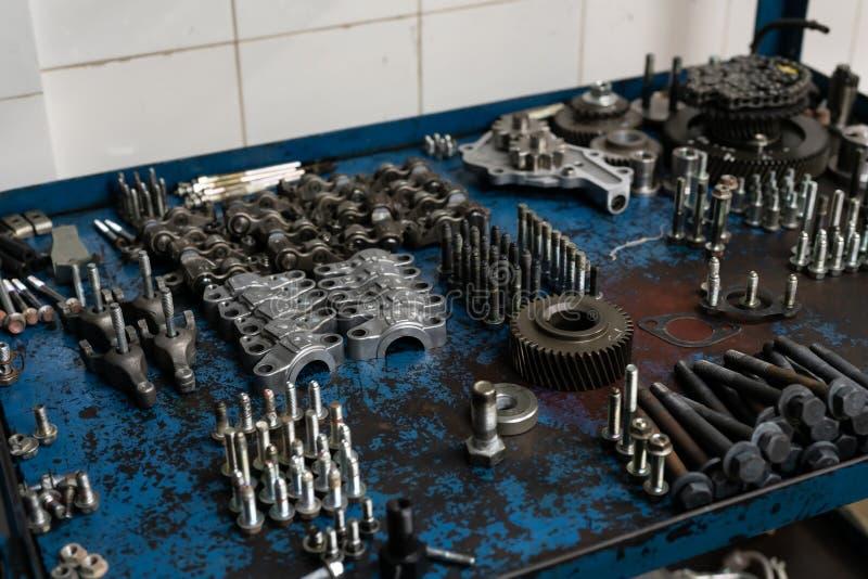 Componentes del motor Piezas del motor, tuercas, tornillos, cojinetes y estrellas del diferencial en el armario de la mesa imagenes de archivo