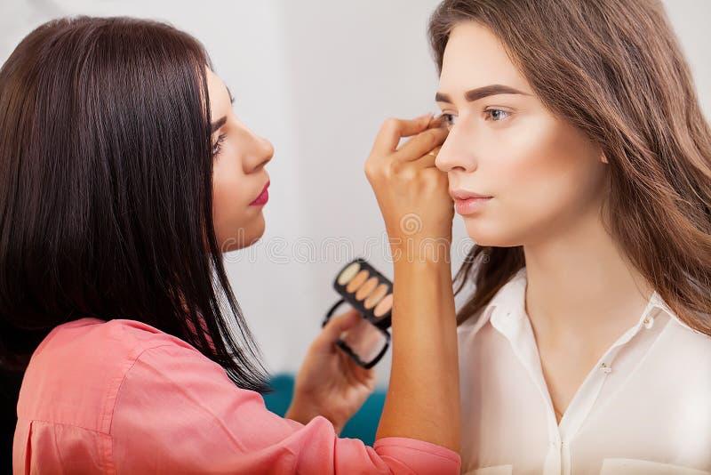 Componga al artista que hace maquillaje profesional de la mujer joven cerca del espejo en estudio de la belleza fotografía de archivo libre de regalías