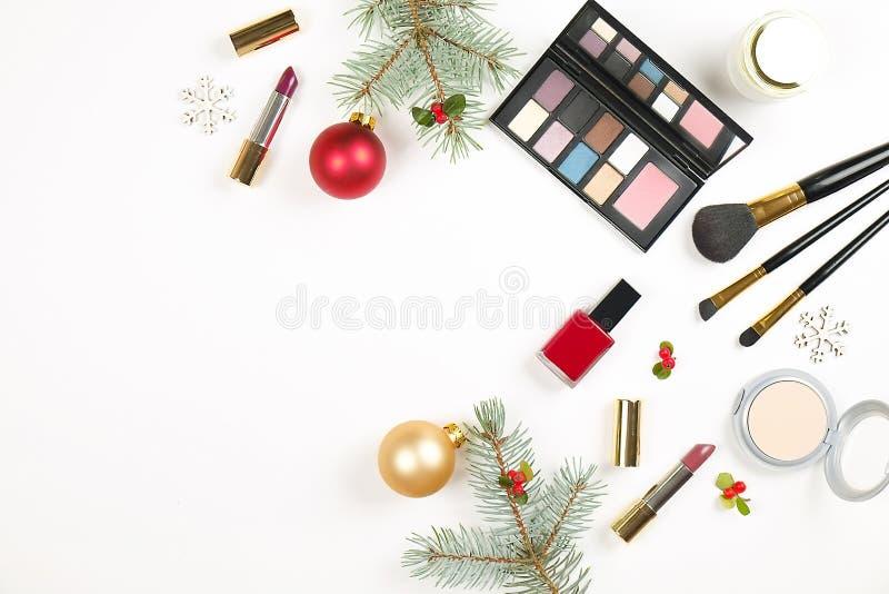 Componga el cosmético determinado con la decoración de la Navidad en la endecha blanca del plano del fondo fotos de archivo