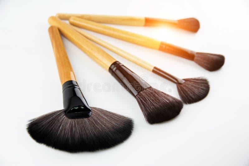 Componga el sistema de cepillo puesto en el fondo blanco los diversos cepillos profesionales de los cosméticos para hacen u fotos de archivo