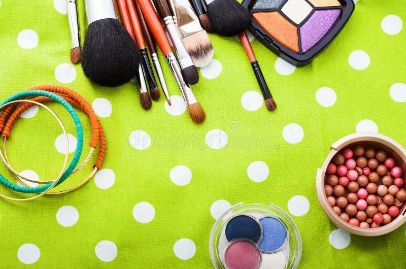 Componga gli strumenti Ombretti Cosmetici sul fondo verde dei pois Vista superiore Derisione su, spazio della copia immagine stock libera da diritti