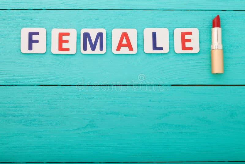 Componga il concetto Rossetto rosso Femmina di parola su fondo di legno blu Vista superiore fotografie stock