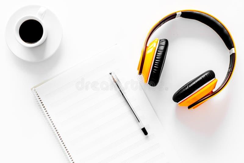 Componga la musica Cuffie, note di musica e tazza di caffè sulla vista superiore del fondo bianco fotografia stock