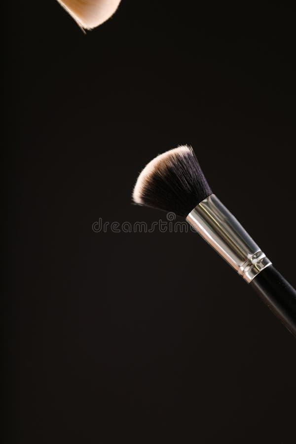 Componga le spazzole cosmetiche con polvere per arrossire esplosione su fondo nero immagini stock